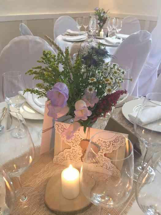 Blumendekoration auf einen runden Festtisch der Hochzeitslocation Haus Schnede.