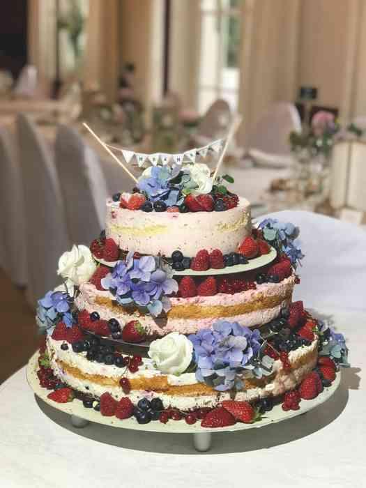 Dreistöckige Hochzeitstorte mit Erdbeeren, Blaubeeren, weißen Rosen und Hortensienblüten in der Hochzeitslocation Haus Schnede.