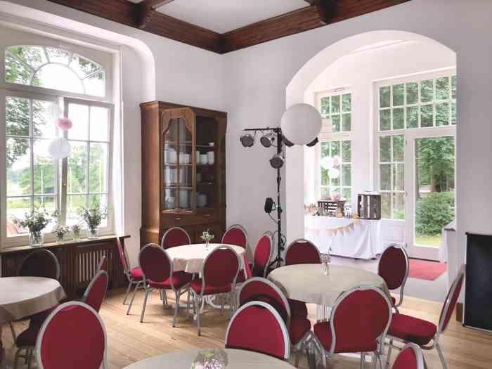 Der Salon mit großen Fenstern und Zugang zur Veranda der Hochzeitslocation Haus Schnede.