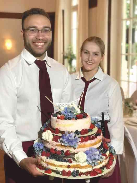 Dreistöckige Hochzeitstorte mit Erdbeeren, Blaubeeren, weißen Rosen und Hortensienblüten serviert vom Serviceteam der Hochzeitslocation Haus Schnede.