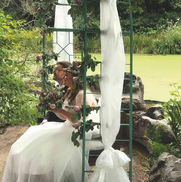 Brautpaar mit Rosenbogen Hochzeitslocation Haus Schnede.