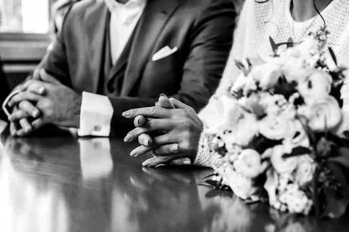 Brautpaar am Tisch des Standesbeamten mit gefalteten Händen.