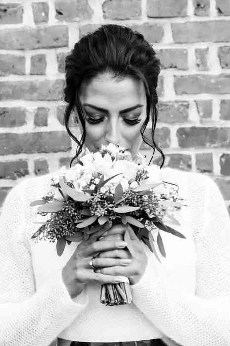 Braut hält sich den Brautstrauß vor das Gesicht.