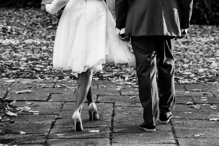 Brautpaar spaziert einen Weg entlang.