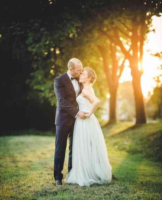 Brautpaar in Landschaft bei Sonnenuntergang.