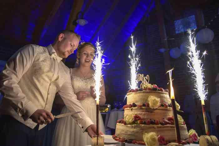 motiv pictures Braut und Bräutigam auf der Hochzeitsfeier beim Anschneiden der Hochzeitstorte