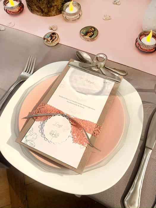 Hochzeitstisch mit Teller, Menuekarte und Dekoration.
