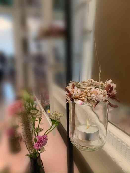 Hochzeitsdeko Windlichter mit Blütenkranz geschmückt.