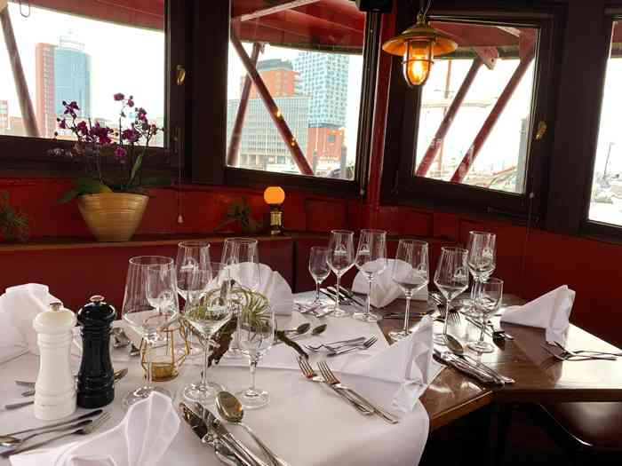 """Mit Blick auf die Elbphilharmonie sind die Tische im Bug des """"Das Feuerschiff"""" festlich eingedeckt."""